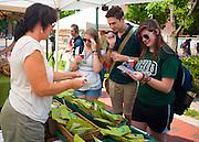 Maureen Burns-Hooker offers samples of tea to freshman students Danielle Keeton-Olson, Jacob Cran, and Christie Bening at the OU Mini Farmer's Market in Howard Park on Friday, September 7, 2012.