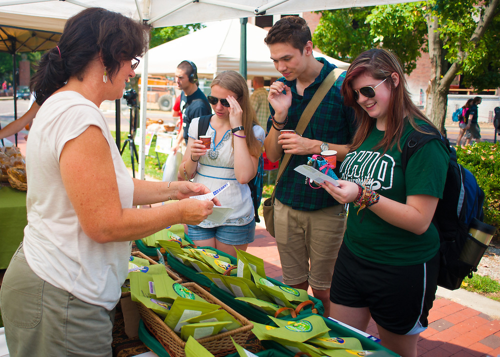 Maureen Burns-Hooker offers samples of tea to freshman students Danielle Keeton-Olson, Jacob Cran, and Christie Bening at the OU Mini Farmer's Market in Howard Park on Friday, September 7, 2012.