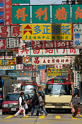 Many shop signs with Chinese characters hanging in Shanghai Street in Kowloon district of Hong Kong