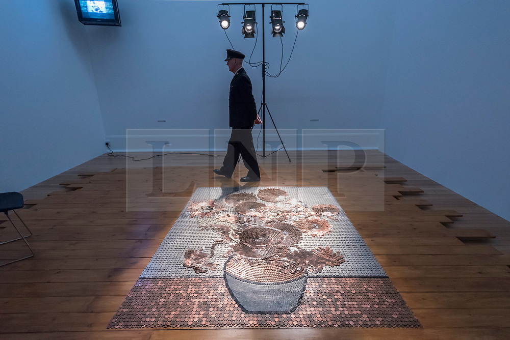 """© Licensed to London News Pictures. 01/04/2019. LONDON, UK.  """"Bureau de Change"""", 1987, by Rose Finn-Kelcey is unveiled at Tate Britain.  Coinciding with """"The EY Exhibition:  Van Gogh and Britain"""", the live installation consists of 1,000 worth of coins laid out on the floor in the image of Vincent Van Gogh's """"Sunflowers"""".  The installation is overseen each day by an actor posing as a security guard, with visitors viewing the scene from a platform and will be in place 1 Aptil to 11 August 2019.  Photo credit: Stephen Chung/LNP"""