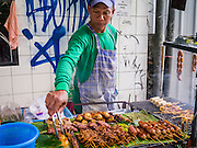 "04 OCTOBER 2012 - BANGKOK, THAILAND: A grilled meat vendor works at his stand on Sukhumvit Rd in Bangkok, Thailand. He sells grilled chicken's feet and Thai sausage. Thailand in general, and Bangkok in particular, has a vibrant tradition of street food and ""eating on the run."" In recent years, Bangkok's street food has become something of an international landmark and is being written about in glossy travel magazines and in the pages of the New York Times.       PHOTO BY JACK KURTZ"