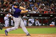 Apr 29, 2016; Phoenix, AZ, USA; Colorado Rockies catcher Nick Hundley (4) hits a solo home run during the fourth inning against the Arizona Diamondbacks at Chase Field. Mandatory Credit: Jennifer Stewart-USA TODAY Sports
