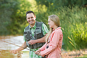 Father and daughter sharing a moment of laughter while fly fishing together at the Billingsley Creek Lodge and Retreat in Hagerman, Idaho.