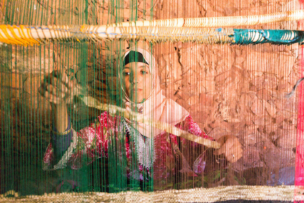 Portrait of key keeper Hassan's wife weaving a carpet using a traditional loom, Taliouine province of the Souss Massa Draa, Southern Morocco, 2016-05-25.<br /><br />Wool is at the heart of most rural communities in Morocco, with carpet weaving being carried out on traditional vertical and horizontal looms, which can be dismantled and taken from place to place. <br /><br />The carpets are woven by hand, often by female artisans, taking hours or days depending on size and design. Traditions and culture differs within the native Amazigh and Berber tribes living across Morocco and the colors, patterns and designs of traditional Berber carpets vary.<br /><br />The journey to find each agadir is really the fun part. Whether it's stopping to meet interesting characters as you ask for directions in remote villages, finding yourself being invited to drink tea at a home during rains, or laughing as you weigh up the tales told by key keepers concerning the secrets of the agadirs, these incredible structures make for an amazing thread to any trekking route through the Anti Atlas.