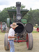 A man cleans the boiler tubes in his antique J.I. Case steam tractor; Rock River Thresheree, Edgerton, Wisconsin; 2 Sept 2013