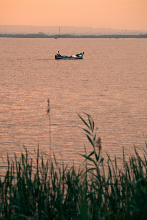 Fisherman on his boat at La Albufera National Park, in Valencia, Spain.