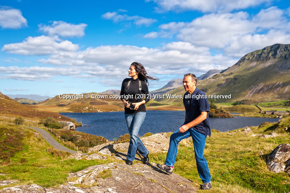 Couple walking with lakes and Cadair Idris in background<br /> Llynnau Cregennen<br /> Snowdonia<br /> Gwynedd<br /> Mid<br /> Walking<br /> Activities and Sports