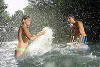 Couple splashing water at each other in forest river side view