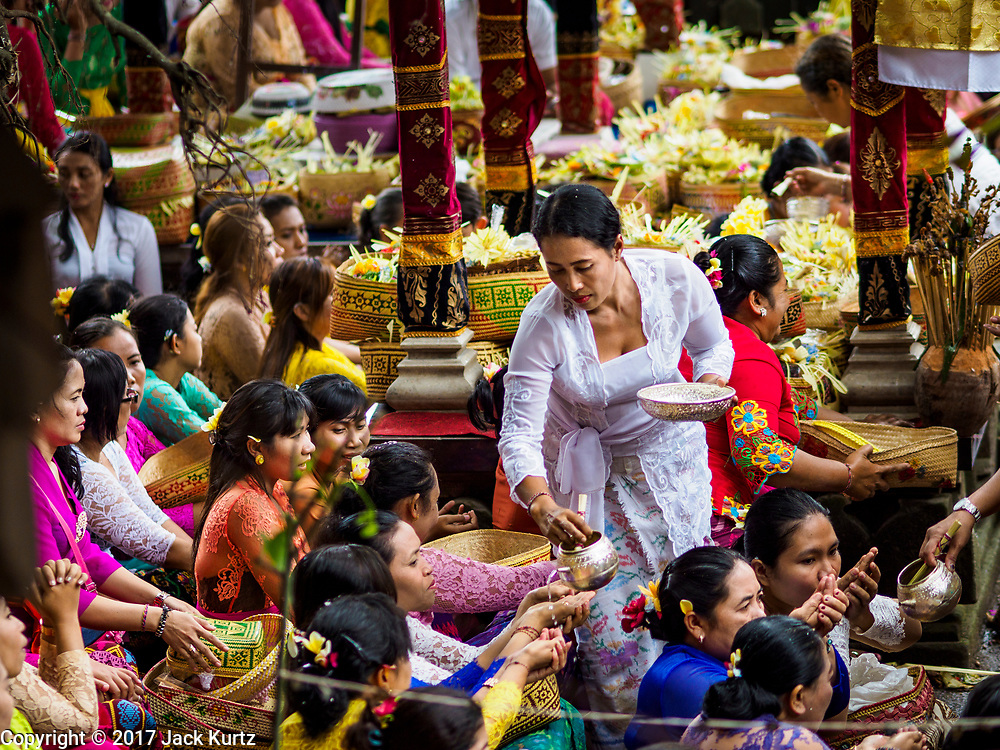 """02 AUGUST 2017 - UBUD, BALI, INDONESIA: People get holy water during the """"Merchants' Day"""" ceremony at the Pura (Temple) Melanting Pasar Ubud, the small Hindu temple in the Ubud market. It's a day that merchants throughout Ubud come to the temple to make offerings and pray for prosperity.    PHOTO BY JACK KURTZ"""