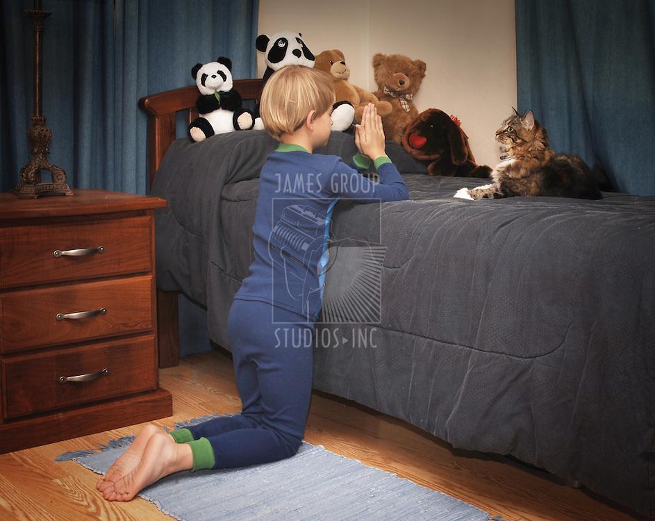 boy kneeling at bedside saying prayers in pajamas