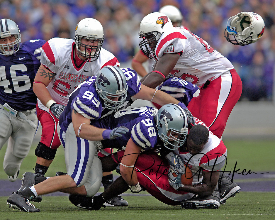 Kansas State University -- Illinois State running back Pierre Rembert (5) has his helmet knocked off, after getting hammered by Kansas State defenders Ian Campbell (98) and Steven Cline (99) at Bill Snyder Family Stadium in Manhattan, Kansas.