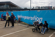 Families rest before the start of the canoe slalom heats at the Lee Valley White Water Centre, north east London, on day 3 of the London 2012 Olympic Games. The slogan 'Inspire a Generation' is written on a London 2012 banner asking Britons to help encourage and influence the next generation of young people into sport, to promote health and confidence in times of economic austerity plus poor health and diet.