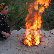 A woman lights the fire in the tandoor outdoor oven for baking bread, early in the morning, Nokhur village, Turkmenistan