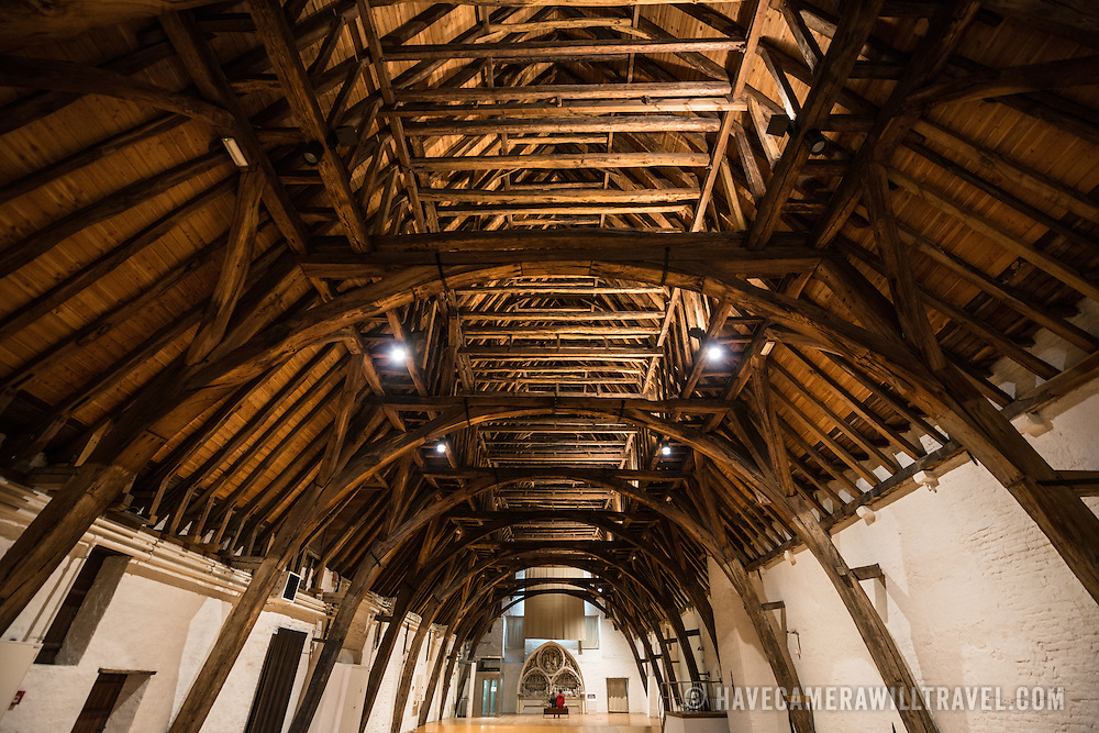 Original wooden roof supports exposed in a top level hall at Old St John's Hospital in Bruges, Belgium. Old St. John's Hospital is one of Europe's oldest surviving hospital buildings that dates to the 11th century. It originally treated sick pilgrims and travelers. A monastery and convent was later added. It is now a museum.