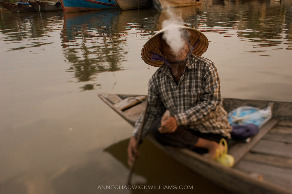 Hoi An, Vietnam boater smokes.