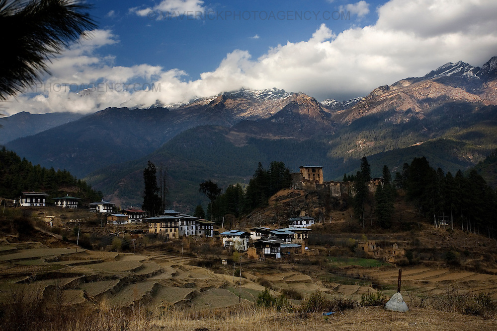 The ruins of old Drukgyel dzong (fortress of victory) stands alone on a hill (middle) Paro.  Commonly described as the last Himalayan Shangrila, Bhutan is a country of unique serenity, harmony, and beauty. Nestled between India, China, and Tibet, this independent country whose name translates as 'the Land of the Thunder Dragon' has for the past 300 years  proactively followed a policy of isolation and cultural protection. Travel in and out of the country is strictly regulated, and the impact of outside influences on the local culture is carefully monitored. Spirituality is an important aspect of Bhutanese culture, with Buddhism being interlinked with everyday life. Gross National Happiness (GNH), as opposed to GNP/GDP, forms the cornerstone of its development strategy which focuses on a holistic development strategy that complements its cultural and Buddhist spiritual values.