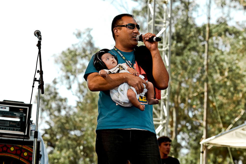 MC  onstage with baby at 12th Annual Power to the Peaceful Festival in Golden Gate Park, in San Francisco, CA.  Copyright 2010 Reid McNally.