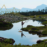 dramatic yoga pose on shore of small mountain lake woman reflection in water