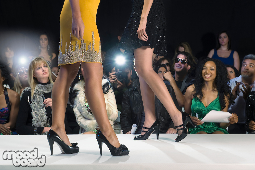 Low section of women walking in black high heeled shoes on fashion catwalk
