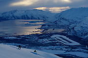 Two snowboarders on the last run of the day above Valdez, Alaska