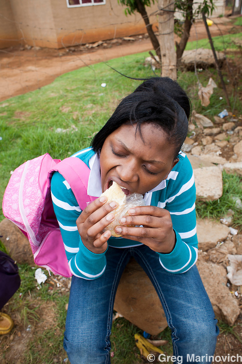 South Africa, Orange Farm, Drieziek, November 22, 2011. South Africans eating popular foods.  Mvhango Tuck Shop sells ikota or white bread quarters filled with chips, processed meat and cheese . Three sisters Nthombi , Patricia and Thembu Ndlovu eat the R10.50 ikhota (bread, chips, polony, Russian and vienna, with tomato sauce and mustard) All in and around Orange farm. Photo Greg Marinovich / Storytaxi.com