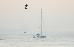 © Licensed to London News Pictures. 04/08/2019. Dover, UK. French inventor Franky Zapata passes near a sailing yacht as he heads to St Margarets Bay near Dover crossing the English Channel on his jet-powered hoverboard. He is hoping to make the 35km crossing with a refueling stop mid channel to reach the English coast after setting off at 6am French time. Photo credit: Peter Macdiarmid/LNP
