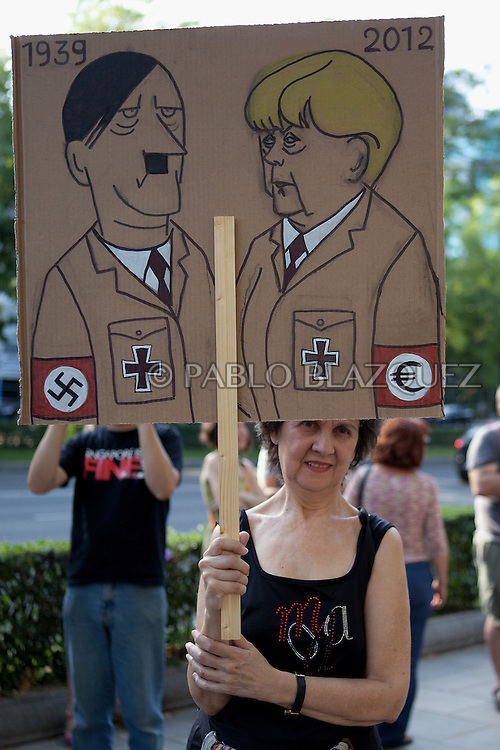 A woman holds a banner during a demonstration against German Chancellor Angela Merkel's official visit to Spain, in central Madrid on September 6, 2012. Merkel is in Spain for talks with conservative Spanish President Mariano Rajoy.