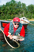 Alaska. Kenai Peninsula. Kenai River. Fly fisher with large rainbow trout. Driftboating.
