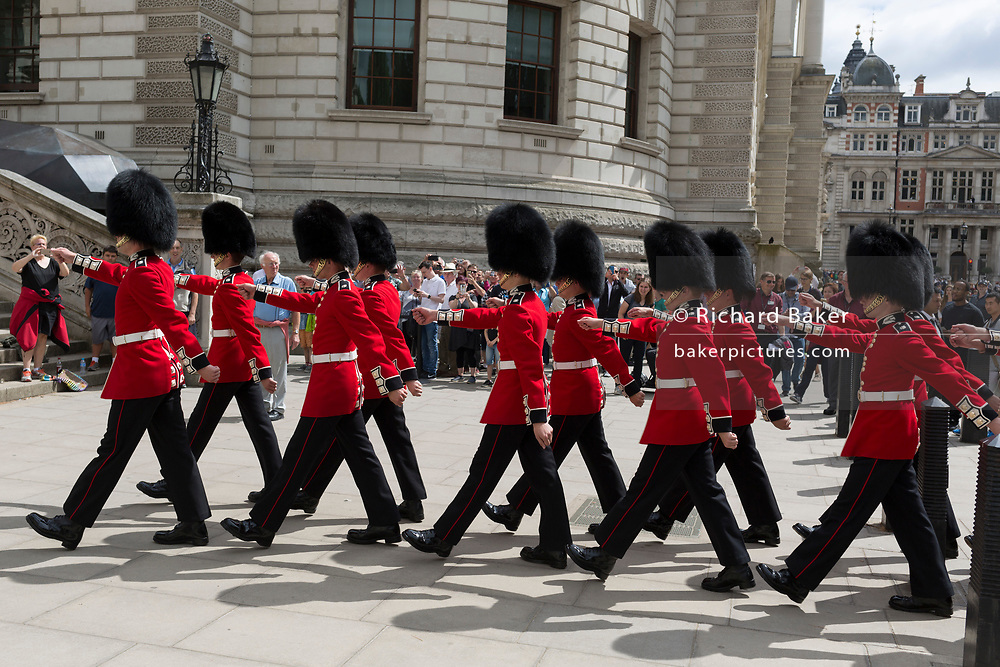 On the 100th anniversary of the Royal Air Force (RAF) and following a flypast of 100 aircraft formations representing Britain's air defence history which flew over central London, guardsmen march up steps between the Foreign Office and the Churchill's War Rooms, on 10th July 2018, in London, England.