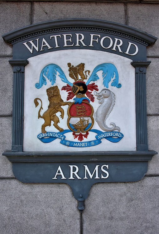 """Coat of Arms of Waterford, Ireland <br /> The coat of arms for Waterford City features a lion and a dolphin below the twin plumage of a knight's helmet. The banner contains the motto, """"The City of Waterford Remains Untaken.""""  This was authored by King Henry VII after Waterford repelled an attack by Perkin Warbeck's army in 1495.  He was a pretender to the English throne. This replica marks the location of the former Waterford Arms Hotel."""
