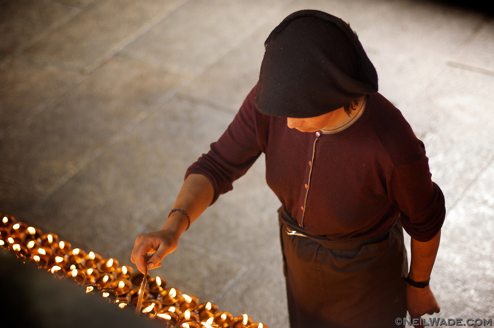 A Tibetan nun lights hundreds of prayer candles at The Jokang, Tibetan Buddhism's most holy temple.  Lhasa, Tibet.
