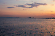 Sunset over bay with Statue of Liberty and Ellis Island NYC