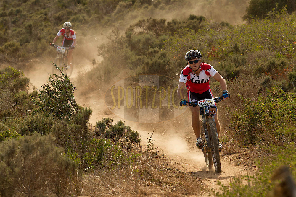 Stuart Briggs from Australia leads Gisela Gartmair from Germany down single track during the Prologue of the 2013 Absa Cape Epic Mountain Bike stage race held at Meerendal Wine Estate in Durbanville outside Cape Town, South Africa on the 17 March 2013..Photo by Greg Beadle/Cape Epic/SPORTZPICS
