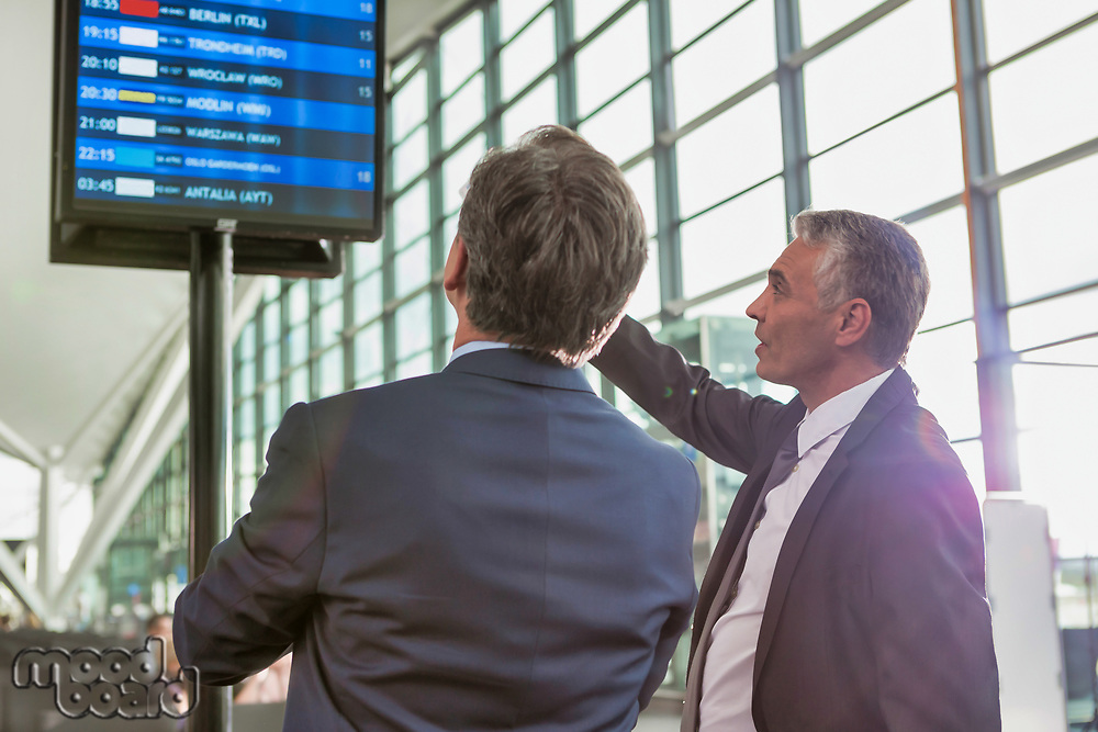 Portrait of mature businessmen looking at their flight on monitor in airport