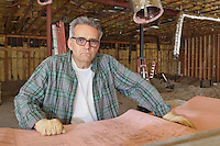Portrait of mature architect wearing glasses with blueprint at construction site