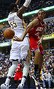 April 21, 2012; Indianapolis, IN, USA; Philadelphia 76ers shooting guard Evan Turner (12) passes the ball around Indiana Pacers center Roy Hibbert (55) at Bankers Life Fieldhouse. Mandatory credit: Michael Hickey-US PRESSWIRE