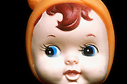 A doll face with a orange hood and spit curls