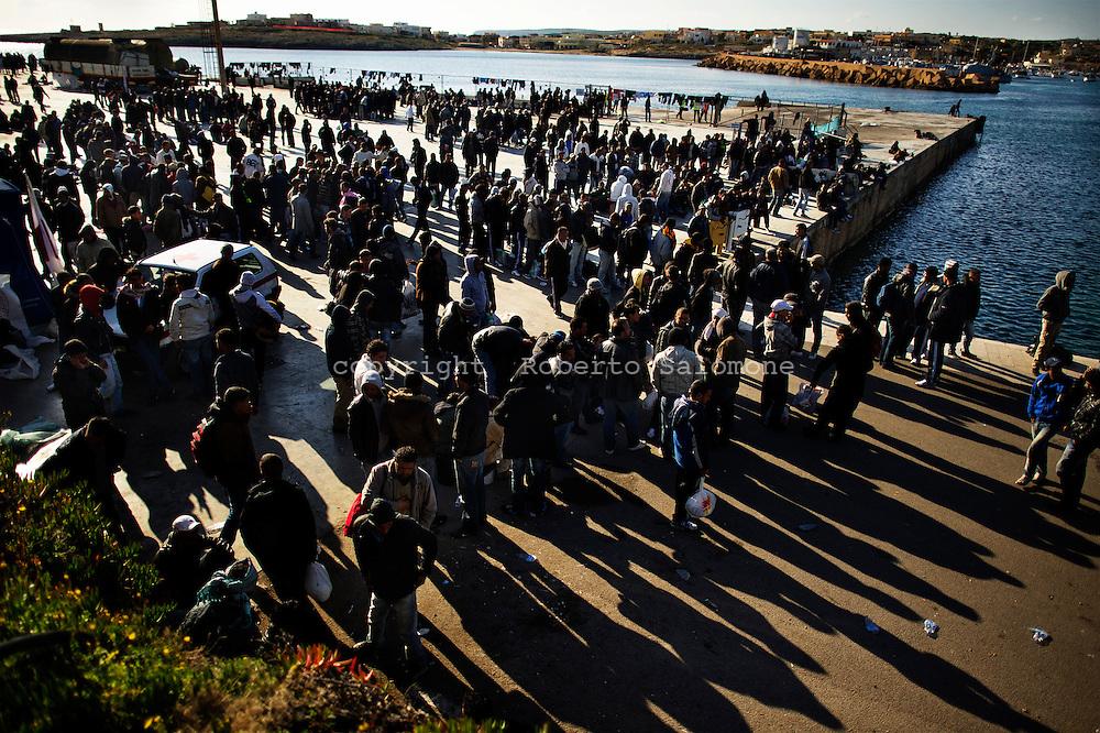 Lampedusa, Italia - 22 marzo 2011. Immigrati nordafricani affallano il piazzale della stazione marittima dell'isola di Lampedusa. Quasi 6000 immigrati sono ospitati tra il centro di accoglienza temporaneo dell'isola e la stazione marittima..Ph. Roberto Salomone Ag. Controluce