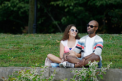 On the Schuylkill River banks a couple is seen relaxing as they attend the 2015 Invisible River Festival on Saturday. (Bastiaan Slabbers/for PhillyVoice)