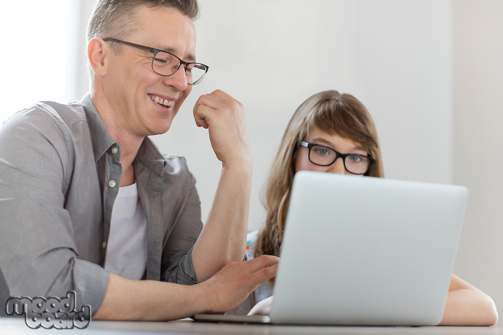 Happy man using laptop with daughter at home