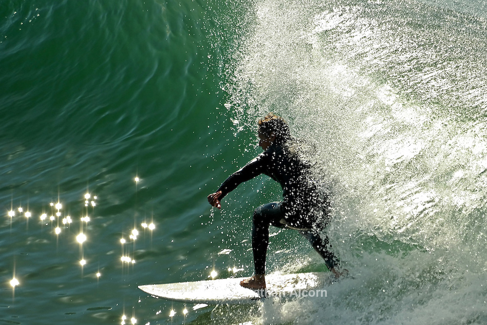 A surfer rides a wave near the Venice Beach pier.
