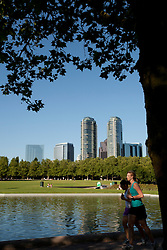 North America, United States, Washington, Bellevue, Bellevue Downtown Park, joggers under trees by fountain with skyscrapers in distance