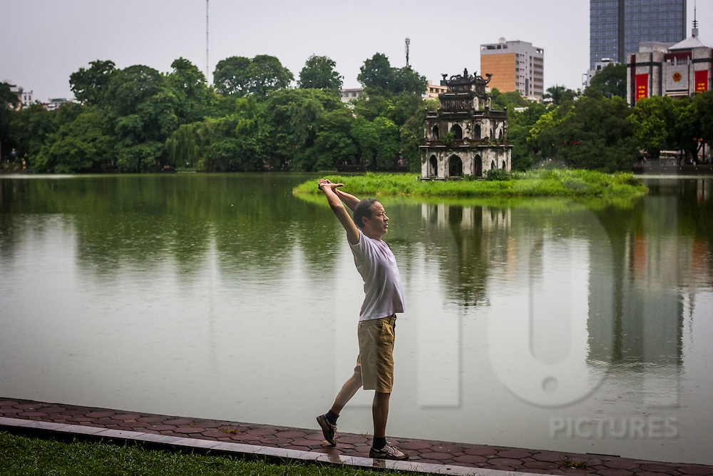 A man exercises in the early morning at Hoan Kiem Lake in Hanoi, Vietnam, Asia
