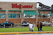 May 23, 2011- Residents of Joplin, Missouri walk across East 20th Street after a Tornado came through the town on Sunday, May 22, 2011. The Walgreens store was a new addition to the town. Credit: David Welker / TurfImages.com.