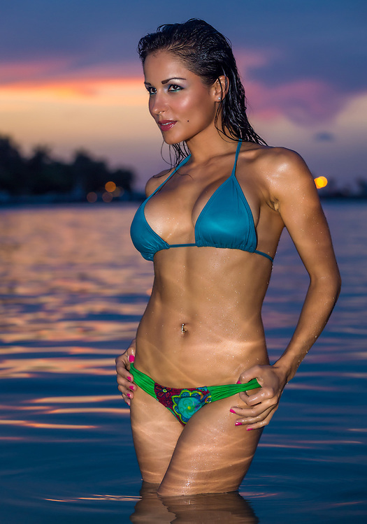 Sexy young female in blue bikini posing in the water during summertime at sunset
