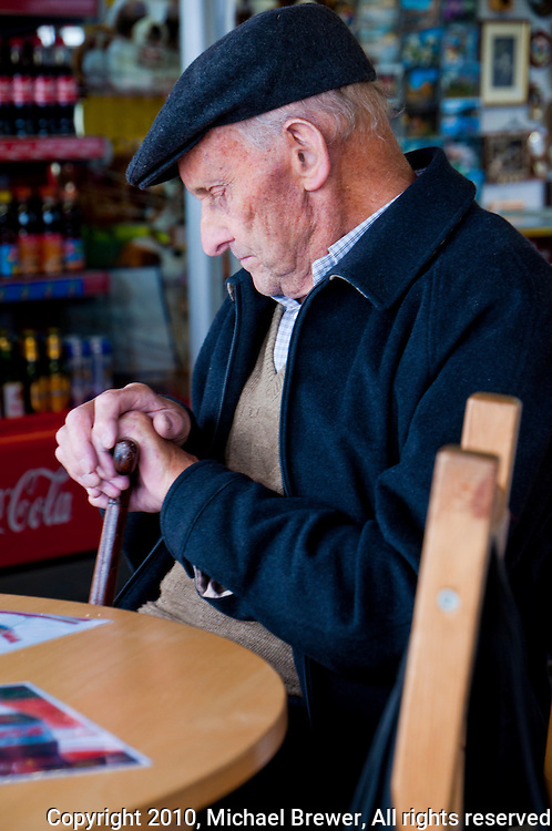 Old man snoozing at a table in a roadside cafe on the Gotthard Pass, Switzerland.