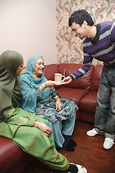 South Asian man handing tea to his mother.