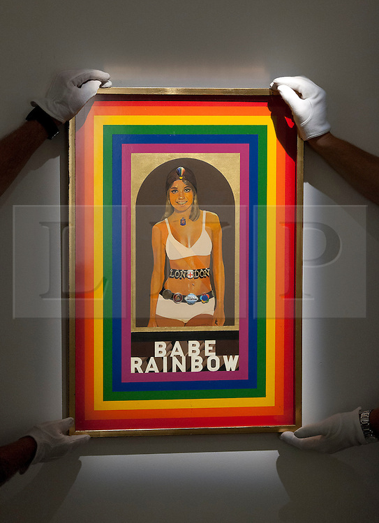 """© Licensed to London News Pictures. 03/09/2013. London, UK. Two Sotheby's employees hold """"Babe Rainbow"""" (1967) by Peter Blake during the press view for an exhibition of art from the 1960's at Sotheby's in London today (03/09/2013). The exhibition, entitled """"The New Situation: Art in London in the Sixties"""" and located at the auction house's New Bond Street building, is open to the public from 4th to the 11th of September 2013. Photo credit: Matt Cetti-Roberts/LNP"""