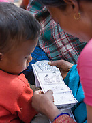 A mother and her son look at the literature illustrating reproductive education distributed by Médecins du Monde health care workers.
