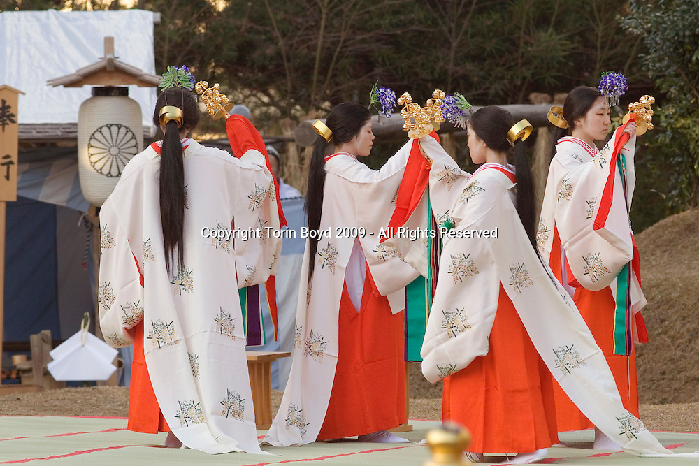 "Dec. 17, 2009: These are miko shrine maidens performing a special Shinto Shaden Kagura dance ritual during the annual On-Matsuri festival, a traditional Shinto religious festival held at the Kasuga Wakamiya Shrine in the ancient Japanese city of Nara, Japan. In older days, miko were considered shamans, but today they take on a more lighter role as priestesses or ceremonial duties. The traditional miko costume is an elaborate multi layered costumed kimono comprised of a red hakama (long, kimono type trousers), a white haori or kimono outer layer, white or red hair ribbons (white symbolizes purity), and in the case of Kasuga Shrine miko, they wear wisteria flowers in their headdress,  symbolic if the shrine's patron the Fujiwara clan. ..This festival which dates back to the twelfth century was first started by Tadamichi Fujiwara, Chief Advisor of the Emperor in 1136 as a way to pray for the eradication of a plague as well as hopes of a bumper crop in the coming year. For many centuries this festival included both Shinto and Buddhist participants, but when Shinto was made the official state religion during the Meiji period (1867-192), the government instituted a policy of separation between Buddhism and Shinto. Ever since, this festival has strictly been a Shinto ceremony held every December 17 on the grounds of Kasuga Taisha Grand Shrine, which Kasuga Wakamiya Shrine is a branch of. During the festival, the Divine Spirit of Wakamiya is temporarily enshrined in the Otabisho, a special shrine set up for just this festival. Several official religious rites are performed throughout the day, as well as the Jidai Gyrotesu, or ""Precession of Eras"" in which parade participants displays traditional Japanese costumes from various era of Japanese history. There are also displays of court music and dance which goes on well into the night."